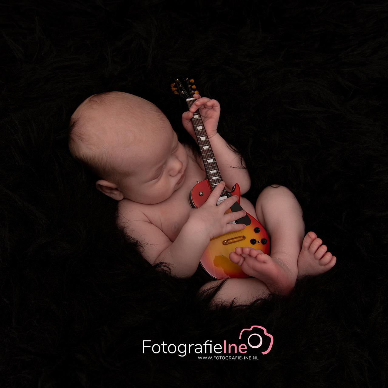 Fotografie Ine newborn baby houdt gitaar vast